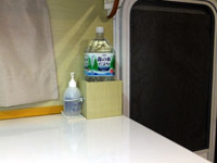 キャンピングカーのキッチンテーブルにミネラルウォーターのペットボトル置き場を設置。手指消毒用のアルコールボトルを固定する場所も作りました