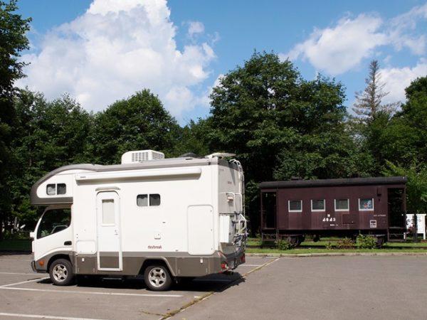 北海道で貨車と写るデイブレイク号マックレー製キャンピングカー