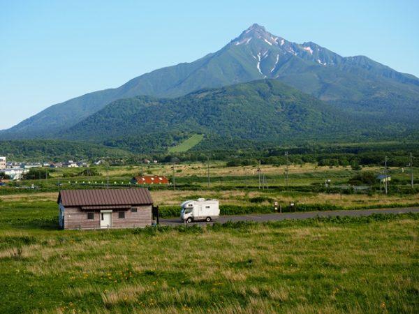 利尻島富士野園地から利尻山とキャンピングカーの画像、エゾカンゾウが咲いている